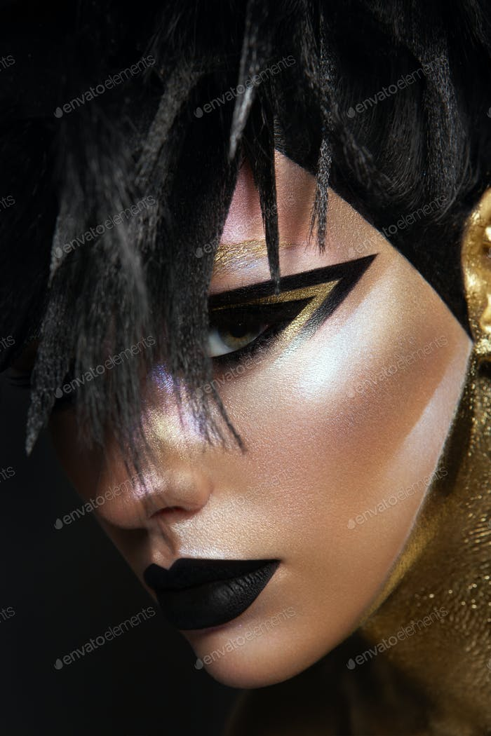 Studio beauty portrait of young woman with black graphic makeup