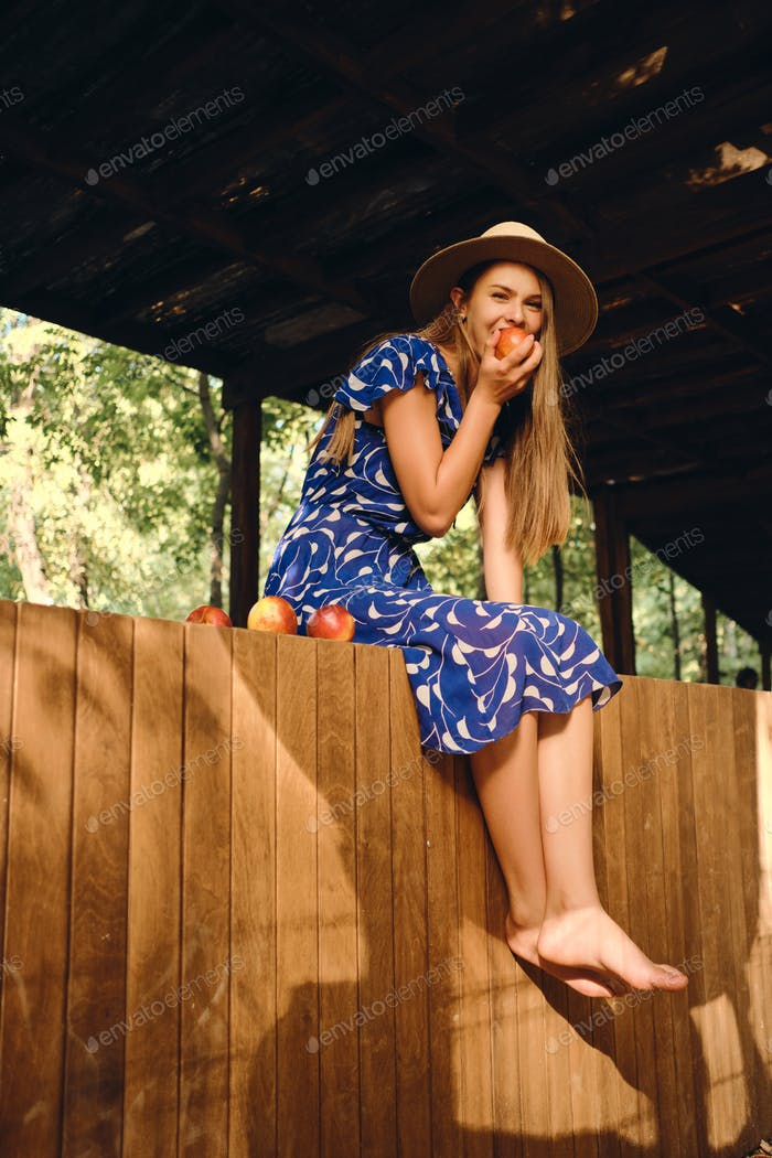 Pretty barefoot girl in blue dress and hat eating peach happily looking in camera