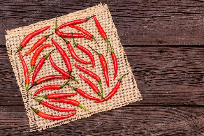 Rote Chilischoten auf Stoff und Holzoberfläche