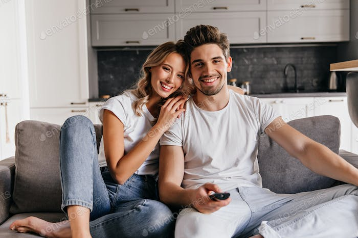 Relaxed man watch TV. Graceful blonde girl sitting on sofa with husband