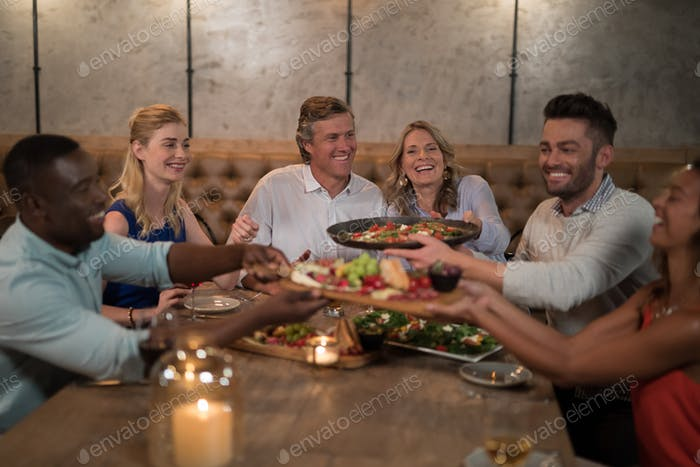 Friends passing food to each other while dining