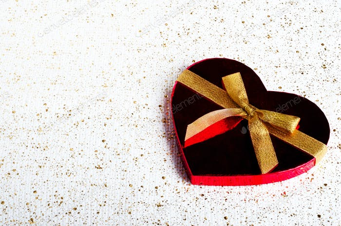 Handmade chocolate candies in red heart shape box with gold bowknot. Copy space