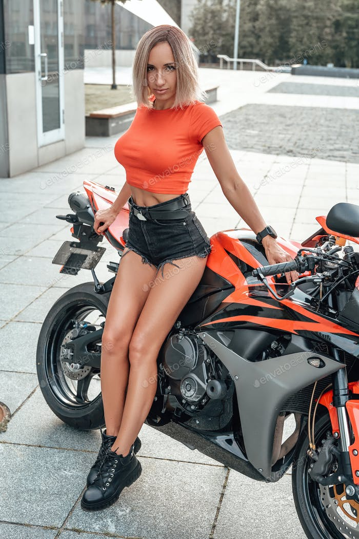 Blond haired woman biker with bike posing outside