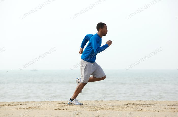 Young male jogger exercising at the beach