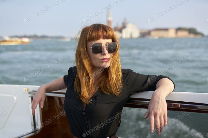 Redhead girl with long black dress, sunglasses and cowboy boots standing on yacht in Venice