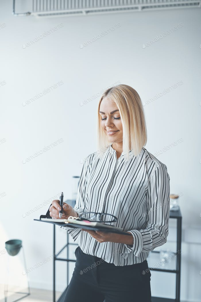 Young businesswoman writing notes while standing in an office