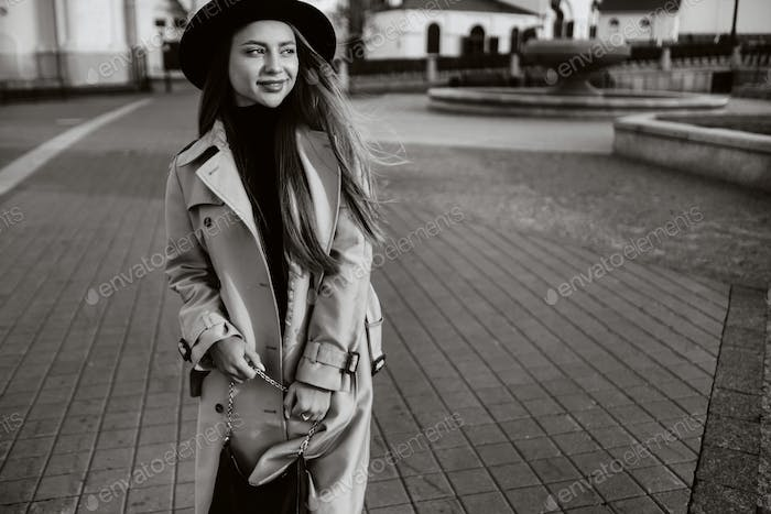 Stylish young woman in a beige coat and black hat on a city street. Black and white photo.Autumn