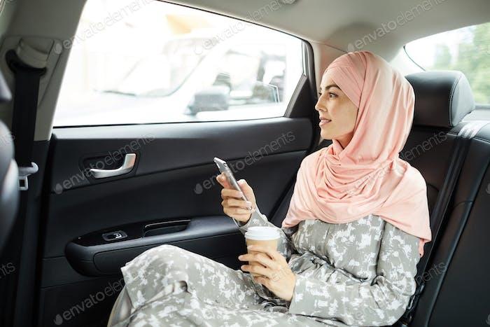 Islamic woman using gadget in taxi