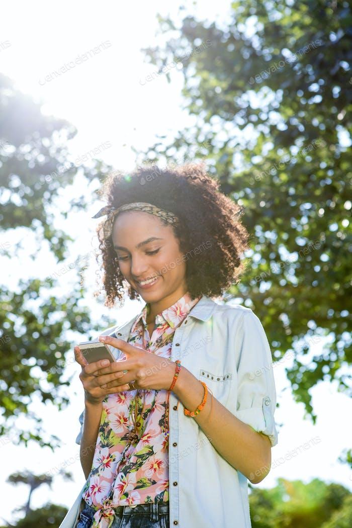 Bastante hipster Uso su teléfono inteligente en un Día de verano