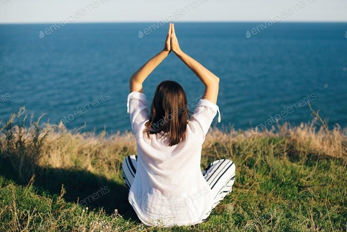 Happy boho woman practicing yoga and meditation on tropical island