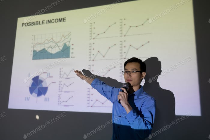 Young broker of Chinese ethnicity pointing at financial graph on large screen
