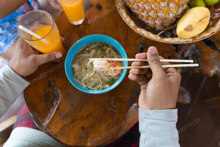Top Angle View Of Man Eating Noodles Chopstick And Drinking Orange Juice Trying Traditional Asian