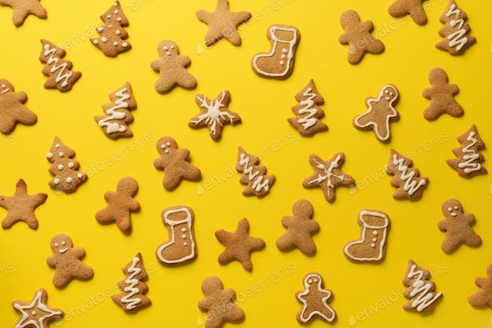 Homemade christmas cookies on yellow background. Pattern of gingerbread men, snowflake, star, fir