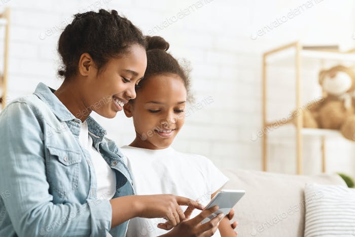 African sisters checking on new mobile application at home