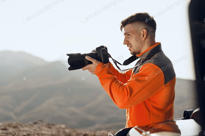 Young man traveler taking photos of mountains with professional camera
