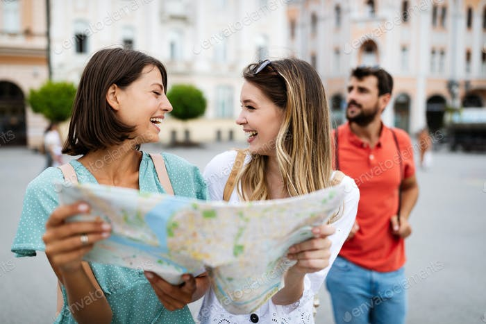 Happy traveling tourists sightseeing with map in hand