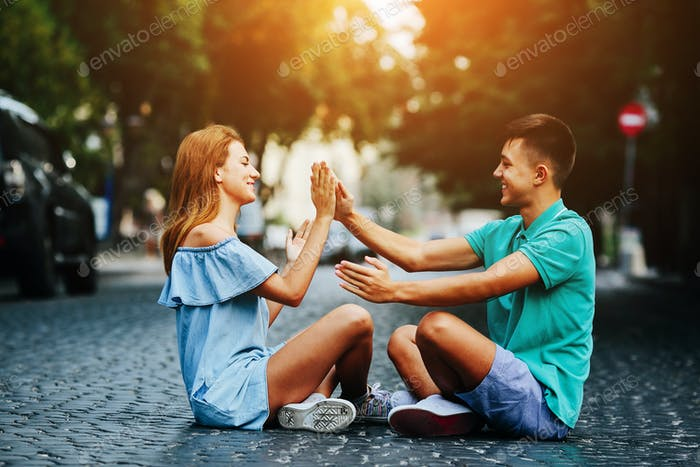 couple sitting on pavement square