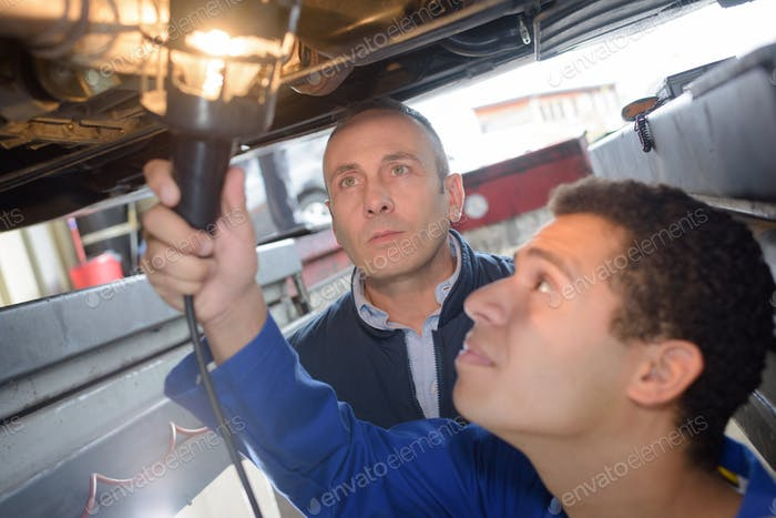 Young mechanic using lamp to inspect vehicle undercarriage