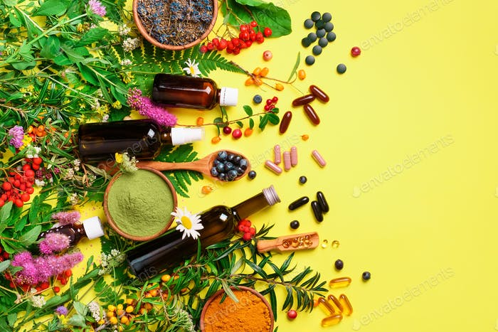 Alternative medicine. Holistic approach. Healing herbs and flowers over yellow background. Top view