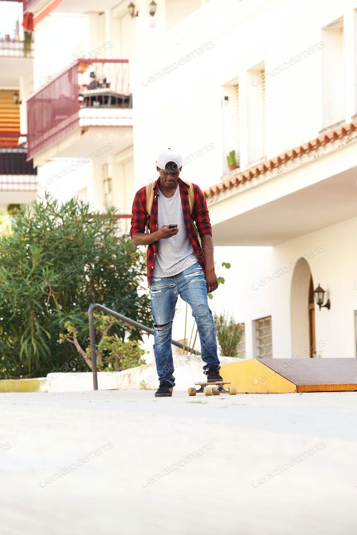 Full length cool young african guy skateboarding and looking at mobile phone