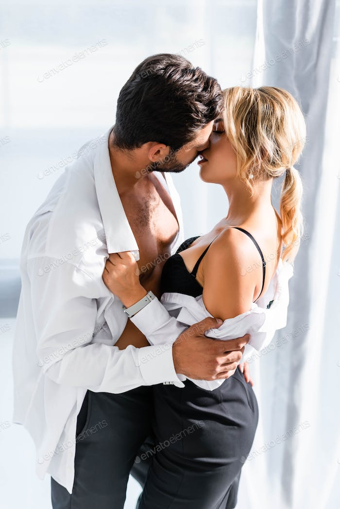 Sexy business couple taking off clothes while kissing in office