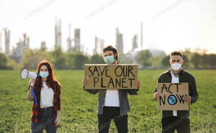 Gruppe von jungen Aktivisten mit Plakaten stehen im Freien durch Ölraffinerie, protestieren