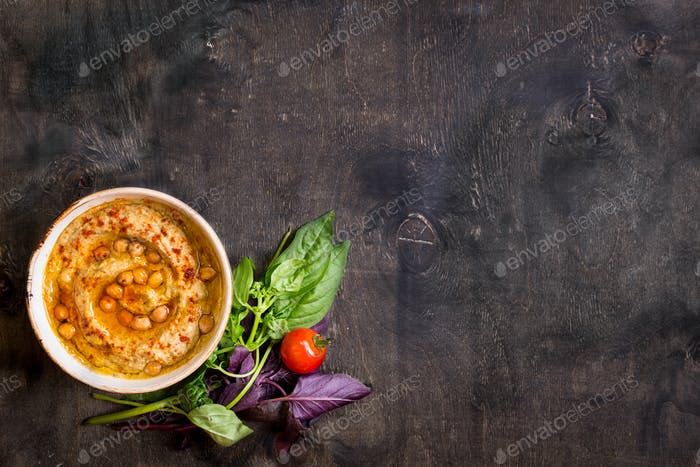 Hummus on a plate with cherry tomatoes and herbs on a dark wooden background