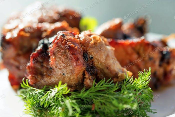 Stücke vom gegrillten Schweinefleisch auf Teller mit Salat