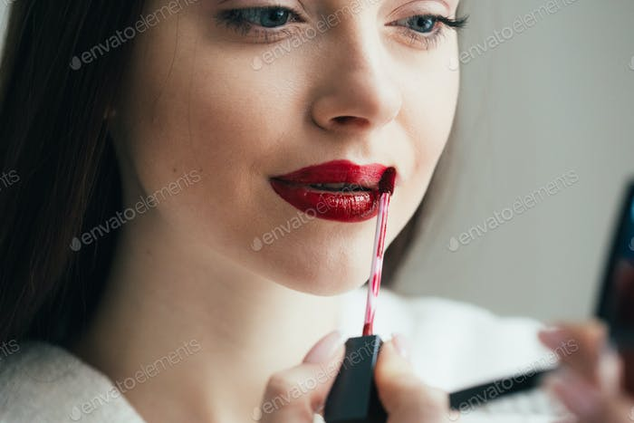 Closeup shot of woman paint her lips by cosmetic brush lipstick on lips