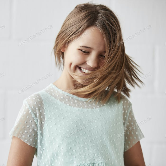 Happy Young Girl Posing In Studio Against White Wall