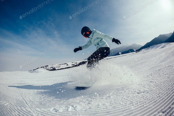 female snowboarder descent on winter mountain slope
