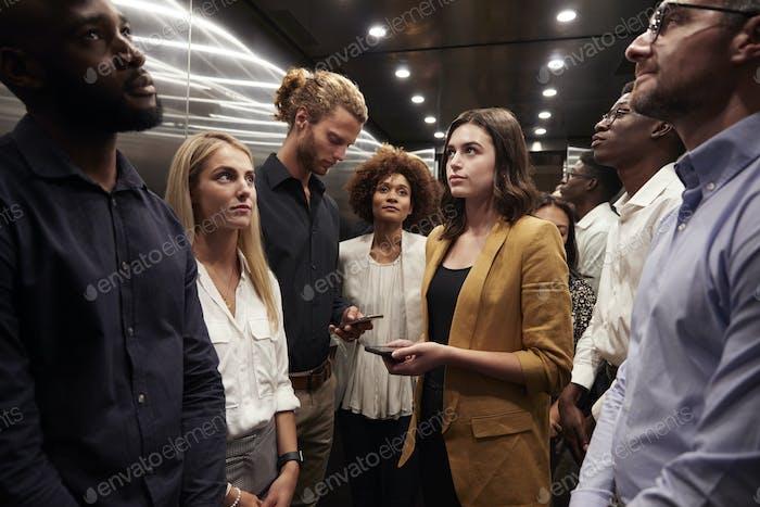 Arbeitskollegen stehen gemeinsam in einem Aufzug in ihrem Büro