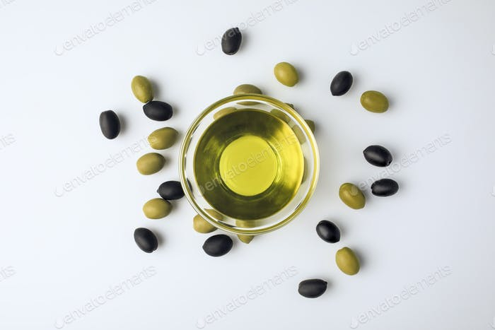 Top view of glass bowl with olive oil and scattered olives around isolated on white