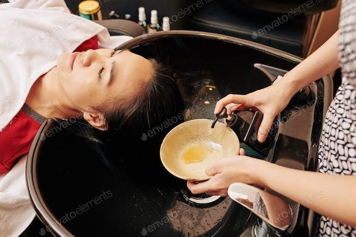 Hairdresser squeezing shampoo