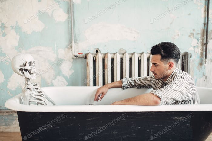 Businessman sitting in bathtub against skeleton