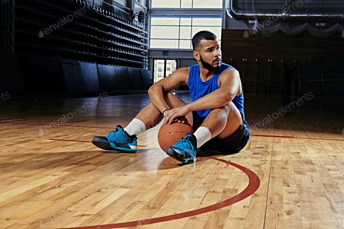 Professional basketball player sits on a floor in a game hall.