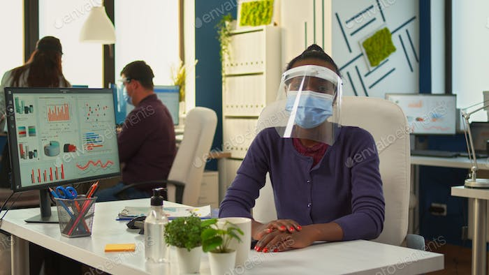 African businesswoman with visor talking at camera
