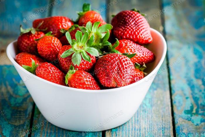 Fresh ripe organic strawberries in a white bowl