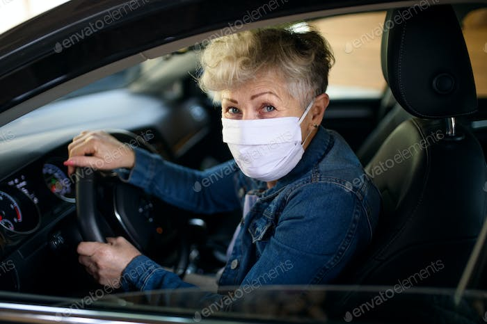 Senior woman driver with face mask in car, quarantine concept
