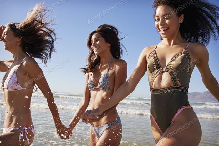 Female Friends Have Fun Running Through Waves On Beach Vacation