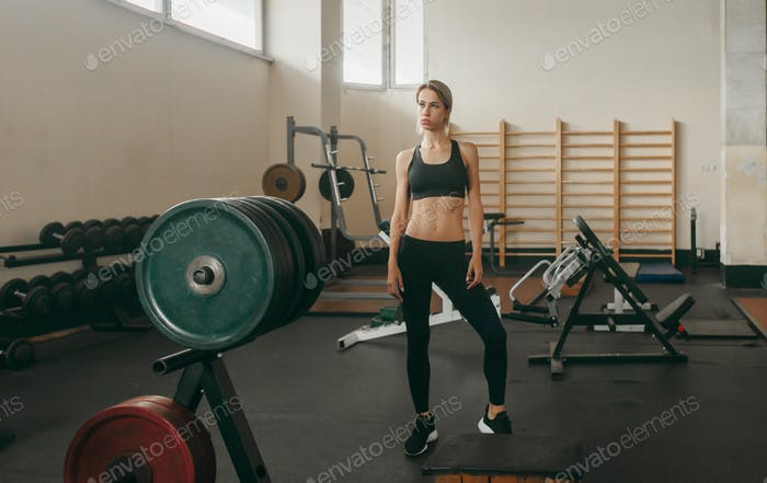 young athletic woman in old gym interior