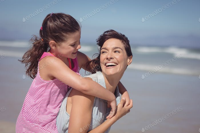 Happy mother piggybacking daughter at beach