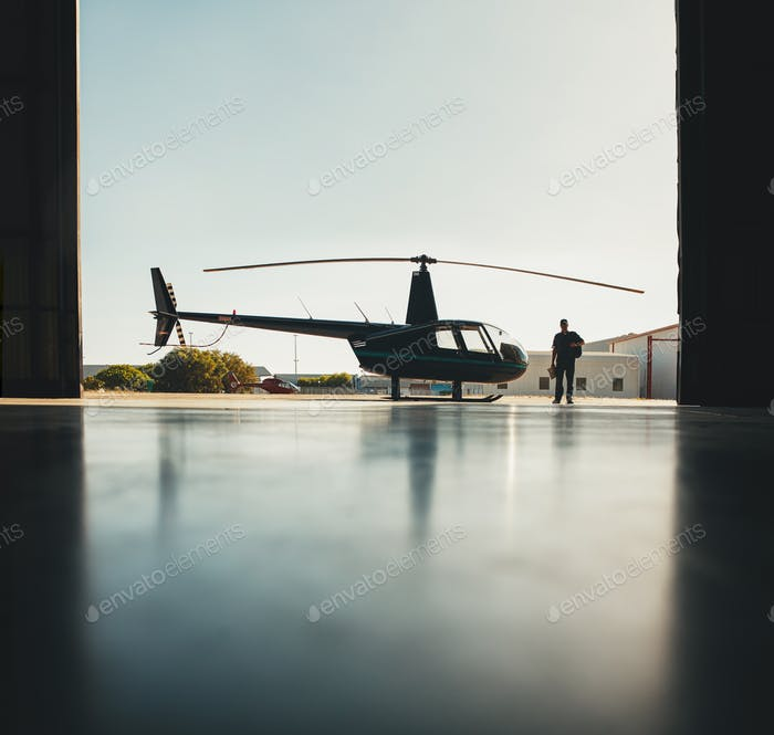 Silhouette des Hubschraubers und ein Pilot im Hangar