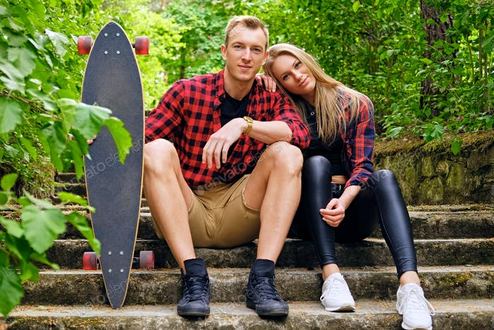 A couple relaxing on the steps after longboard ride.