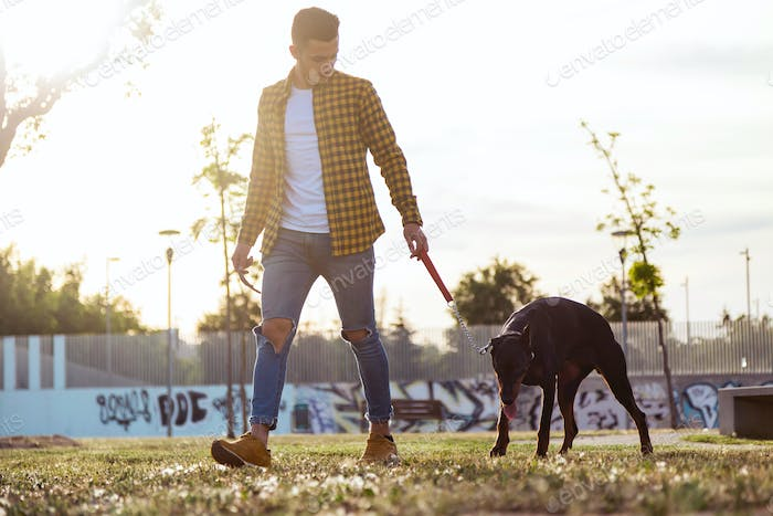 Handsome young man with his dog walking in the park.