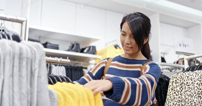 Woman shopping for clothes fashion designer browsing wardrobe
