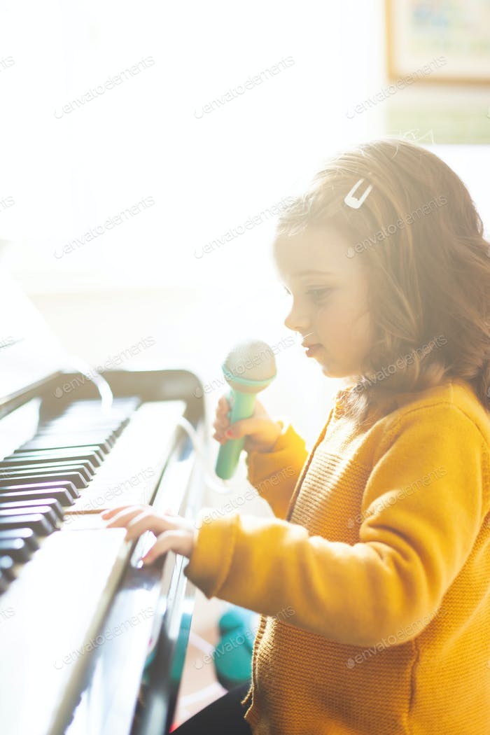 Girl toddler plays with piano and toy microphone.