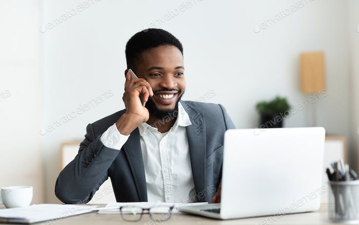 Happy african american employee talking on cellphone at office