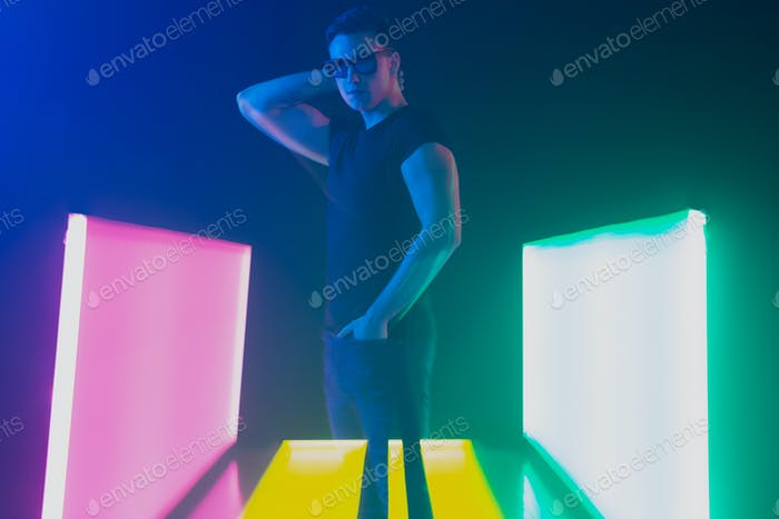 Young caucasian man posing stylish in neon light on dark background