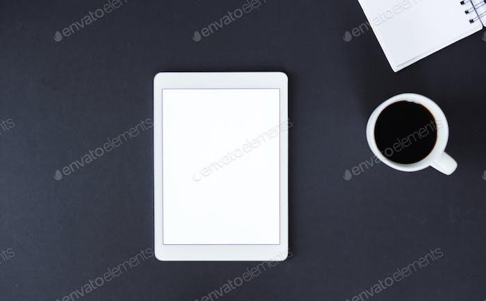 Ein Studio-Shot von Tablet und Kaffee auf schwarzem Hintergrund. Eine Draufsicht. Kopierraum.